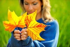 Fille avec des lames d'automne extérieures photos stock