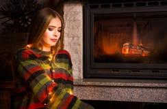 Fille avec des lumières de Noël par la cheminée photographie stock libre de droits