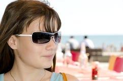 Fille avec des lunettes de soleil à la plage Photographie stock libre de droits