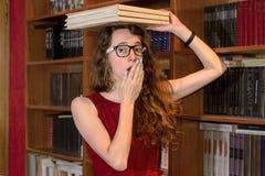 Fille avec des lunettes tenant des livres sur la tête et les bâillements Photographie stock