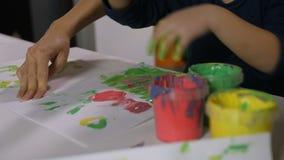Fille avec des mains dans la peinture de doigt de peintures à la classe clips vidéos