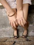 Fille avec des mains sur des genoux Photographie stock libre de droits