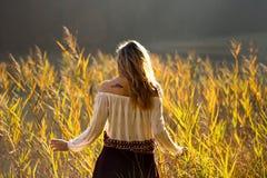 Fille avec des montagnes de tatouage sur l'épaule se tenant et méditant dans le domaine des roseaux/de fille blonde marchant par  photo stock