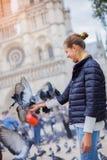 Fille avec des oiseaux près de cathédrale de Notre Dame de Paris à Paris, France Photo stock
