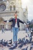 Fille avec des oiseaux près de cathédrale de Notre Dame de Paris à Paris, France Images libres de droits