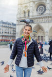 Fille avec des oiseaux près de cathédrale de Notre Dame de Paris à Paris, France Photo libre de droits