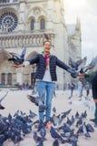 Fille avec des oiseaux près de cathédrale de Notre Dame de Paris à Paris, France Photos stock