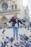 Fille avec des oiseaux près de cathédrale de Notre Dame de Paris à Paris, France Photographie stock libre de droits