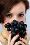 Fille avec des raisins Image stock