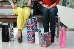 Fille avec des sacs marchant avec son amie au mail et à l'achat Image stock