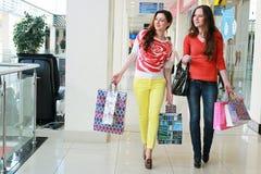 Fille avec des sacs marchant avec son amie au mail et à l'achat Photos stock