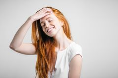 Fille avec des taches de rousseur souriant avec les yeux fermés touchant ses cheveux rouges photographie stock