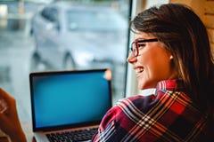 Fille avec des verres riant devant l'ordinateur Images stock