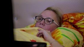 Fille avec des verres se trouvant sur le lit sous une couverture et regardant l'écran d'ordinateur portable clips vidéos