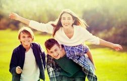 Fille avec deux garçons posant en parc de chute Image libre de droits