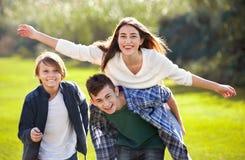 Fille avec deux garçons posant en parc de chute Photos stock