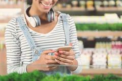 Fille avec du charme joyeuse se tenant avec le smartphone dans le magasin d'aliment biologique Images stock
