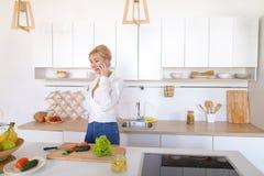 Fille avec du charme parlant au téléphone et préparant le dîner en k élégant Photographie stock