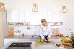 Fille avec du charme parlant au téléphone et préparant le dîner en k élégant Images stock