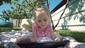 Fille avec du charme posant avec le comprimé sur la pelouse banque de vidéos
