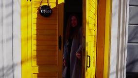 Fille avec du charme se tenant dans la porte de jaune de café et montrant le plat ouvert clips vidéos