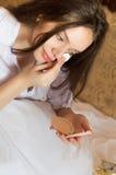 Fille avec du charme se trouvant sur le lit et appliquant la poudre dessus photographie stock