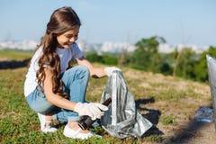 Fille avec du charme tenant un paquet pour des ordures photos libres de droits