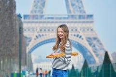 Fille avec du pain français traditionnel savoureux frais (baguette) près de Tour Eiffel images libres de droits