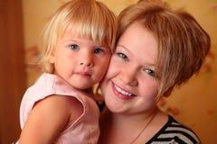 Fille avec l'enfant sur des mains Photos stock