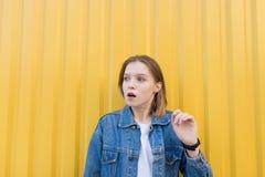 fille avec l'expression étonnée sur les supports de visage sur un fond jaune et des regards au côté photo stock