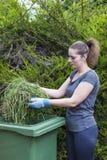 Fille avec l'herbe près de la poubelle verte Images stock