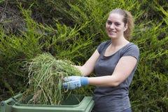 Fille avec l'herbe près de la poubelle verte Photos libres de droits