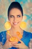 Fille avec l'orangeade et les boucles d'oreille oranges de tranche image libre de droits