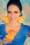 Fille avec l'orangeade et les boucles d'oreille oranges de tranche photographie stock libre de droits