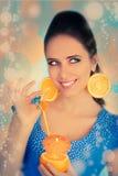 Fille avec l'orangeade et les boucles d'oreille oranges de tranche photo libre de droits