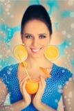 Fille avec l'orangeade et les boucles d'oreille oranges de tranche photographie stock