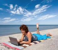 Fille avec l'ordinateur portatif au rivage de mer Image libre de droits
