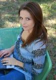 Fille avec l'ordinateur portatif détendant sur l'herbe Photographie stock libre de droits