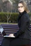 Fille avec l'ordinateur portatif en stationnement Image stock