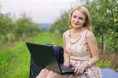 Fille avec l'ordinateur portatif sur la nature Photographie stock
