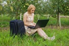 Fille avec l'ordinateur portatif sur la nature Images stock