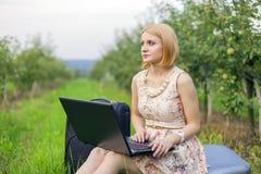 Fille avec l'ordinateur portatif sur la nature Photo libre de droits