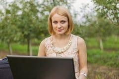 Fille avec l'ordinateur portatif sur la nature Image stock