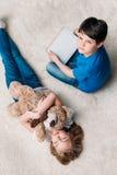 Fille avec l'ours et le garçon de nounours avec le comprimé numérique sur le tapis à la maison Photographie stock