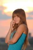 Fille avec l'usure de type occasionnel contre le ciel de coucher du soleil Photographie stock libre de droits