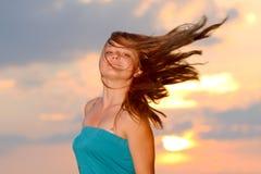 Fille avec l'usure de type occasionnel contre le ciel de coucher du soleil Image libre de droits