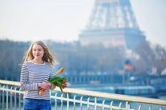 Fille avec la baguette et les tulipes françaises traditionnelles photographie stock libre de droits