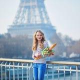 Fille avec la baguette traditionnelle savoureuse fraîche et les tulipes de pain français près de Tour Eiffel images stock