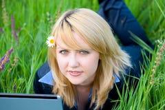 Fille avec la fleur dans le cheveu se trouvant sur l'herbe Photo stock