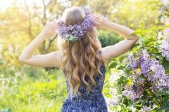 Fille avec la guirlande des fleurs lilas en parc vert photo libre de droits